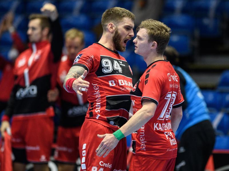 Timo Kastening (r.) und Domagoj Pavlovic jubeln über Melsungens Sieg