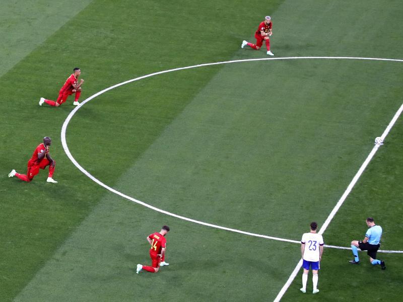 Belgische Spieler und Schiedsrichter Antonio Mateu Lahoz knien vor dem Spiel gegen Russland