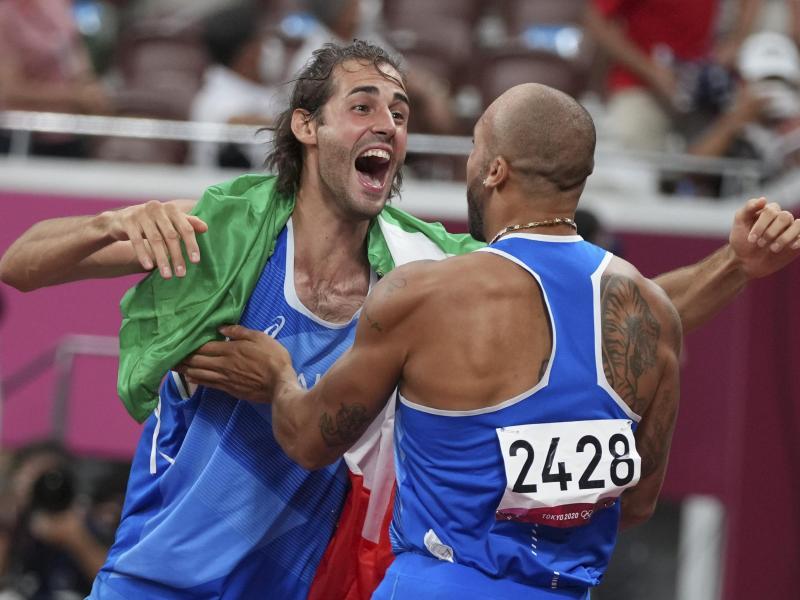 Hochspringer Gianmarco Tamberi (l) und 100-Meter-Sprinter Marcell Jacobs freuen sich gemeinsam über Gold. Foto: Matthias Schrader/AP/dpa