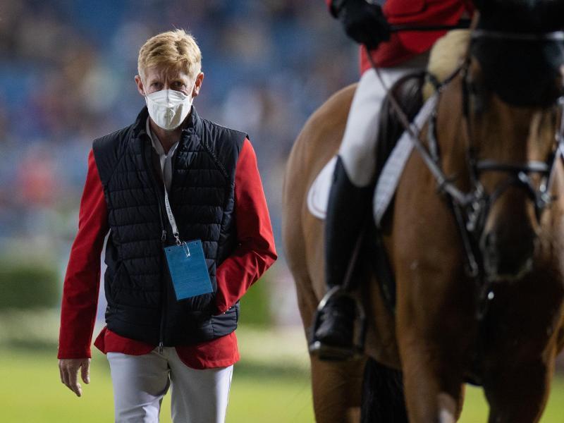 Der verletzte Reiter Marcus Ehning geht neben Daniel Deußer nach dessen Ritt aus dem Stadion