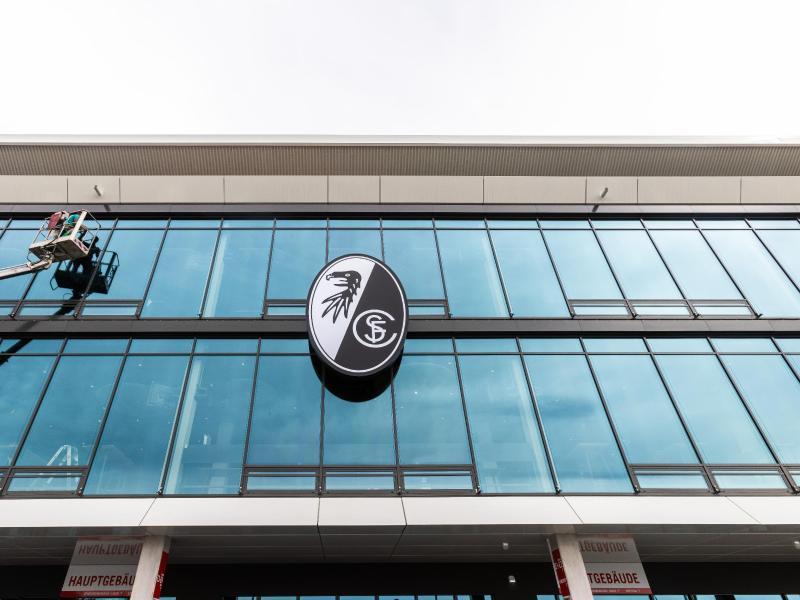 Das Logo des SC Freiburg hängt über dem Eingang des neuen Stadions