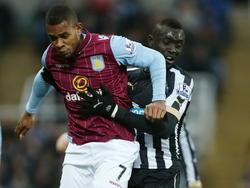 Aston Villa speler Leandro Bacuna (l.) wordt vastgehouden door Newcastle United speler Papiss Cisse (r.). (28-02-2015)