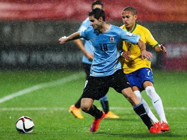 Op het WK Onder 20 Jaar in Nieuw-Zeeland houdt Uruguayaan Gastón Pereiro (l.) Braziliaan Marcos Guilherme van zich af. (11-06-2015)