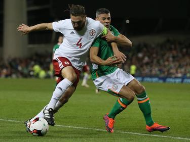 Guram Kashia (l.) trekt zich weinig aan van Jon Walters (r.) tijdens de kwalificatiewedstrijd tussen Georgië en Ierland. (06-10-2016)