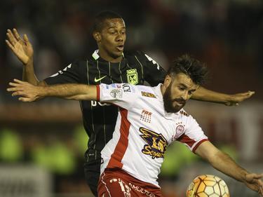 José San Román (r.) probeert tijdens een duel van Huracán tegenstander Jonathan Copete (r.) van Atlético Nacional van de bal te houden. (27-04-2016)