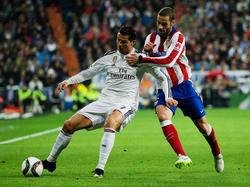 Cristiano Ronaldo (l.) probeert Mario Suárez (r.) van zich af te houden tijdens het bekerduel Real Madrid - Atlético Madrid. (15-01-2015)