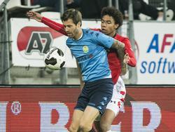Debutant Calvin Stengs (r.) probeert Mels van Driel (l.) de bal te ontfutselen tijdens AZ - ASWH. (14-12-2016)