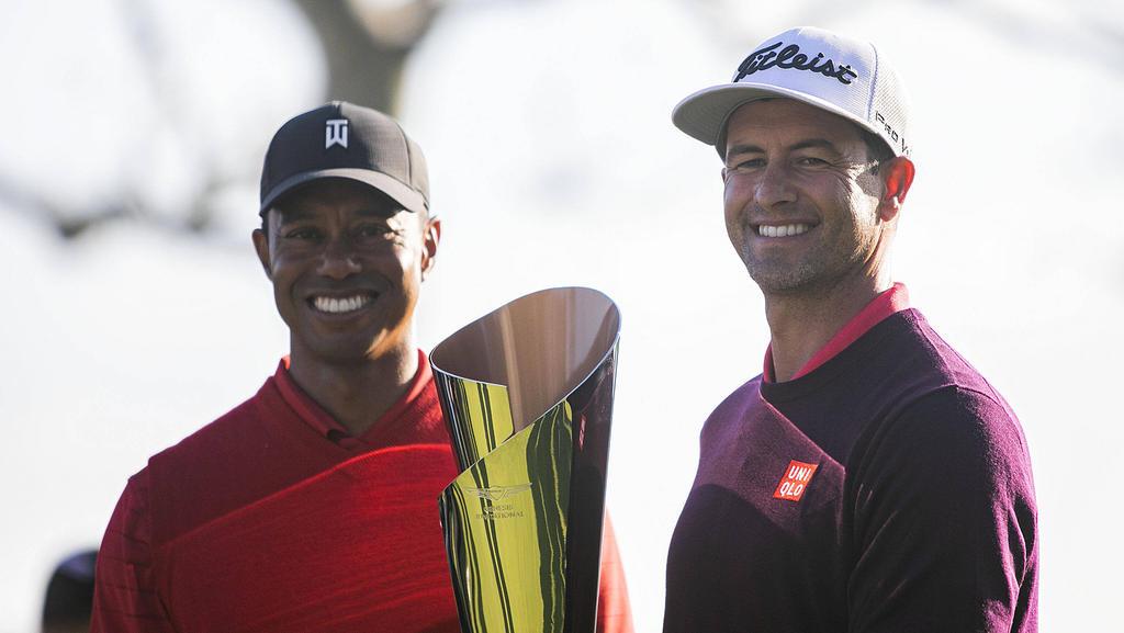 Golf-Stars Tiger Woods (l.) und der Sieger Adam Scott posieren mit der Trophäe