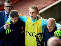 Met een zeer gehavend gezicht wordt Jasper Cillessen van het veld geholpen. De goalie van Ajax breekt zijn neus op de training van het Nederlands elftal na een botsing. (27-03-2016)