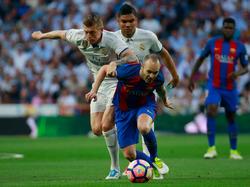 Iniesta wordt in de rug gelopen door middenvelder Kroos van Real Madrid.