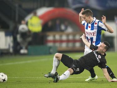 Thomas Bruns (onder) gaat naar de grond tijdens het duel sc Heerenveen - Heracles Almelo. Jukka Raitala staat al met de handen in de lucht. (29-11-2014)