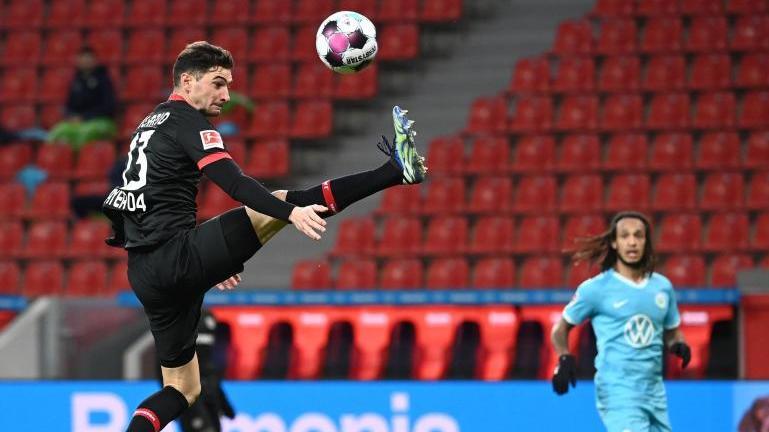 Leverkusens Lucas Alario (l.) nimmt den Ball artistisch in der Luft an
