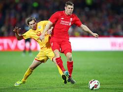 Craig Goodwin (l.) vecht een duel uit met James Milner (r.) tijdens het oefenduel tussen Adelaide United en Liverpool.