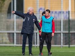 FC Utrecht-trainer Erik ten Hag (l.) geeft instructies tijdens de training, terwijl Jeff Hardeveld (r.) de onderbreking gebruikt om uit te rusten. (11-02-2016)