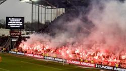 Fans brennen beim Derby zwischen dem FC St. Pauli und dem Hamburger SV Pyrotechnik ab, während eine Anzeigetafel genau davor warnt