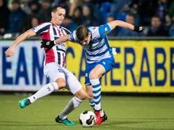 Freek Heerkens (l.) probeert Django Warmerdam (r.) van de bal te zetten. (10-12-2016)
