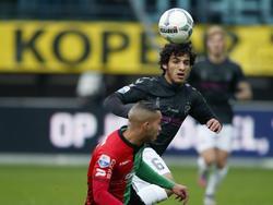 FC Utrecht-middenvelder Yassin Ayoub ziet NEC-speler Gregor Breinburg de bal al zittend wegkoppen. (22-11-2015)