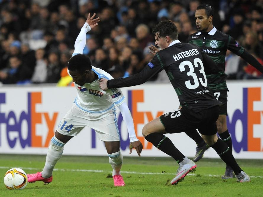 Hans Hateboer (m.) grijpt naar het shirt van Georges-Kévin N'Koudou, om te voorkomen dat de speler van Olympique Marseille uitbreekt. (26-11-2015)