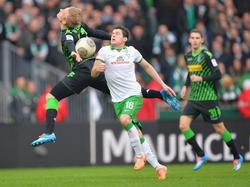 Werder Bremens Zlatko Junuzovic geht am 21. Bundesligaspieltag mit vollem Einsatz in den Zweikampf mit Borussia Mönchengladbachs Oscar Wendt (15.2.2014).
