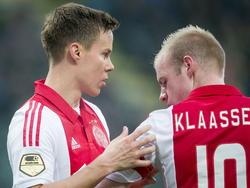 Niklas Moisander (l.) schuift tijdens ADO Den Haag - Ajax de aanvoerdersband om de arm van Davy Klaassen (r.). (30-11-2014)