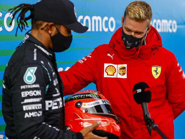 Schumacher (r.) überreicht Hamilton den Helm seines Vaters