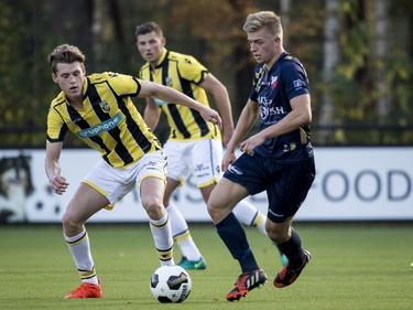 Julian Calor (l.) probeert in te grijpen, als Gwaeron Stout (r.) van Kozakken Boys de bal oppikt op het middenveld. (29-10-2016)