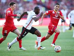 Romeo Castelen (m.) snelt namens Western Sydney Wanderers langs twee tegenstanders van Adelaide United. (01-05-2016)