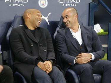 Thierry Henry ríe junto a Martínez en el banquillo belga.