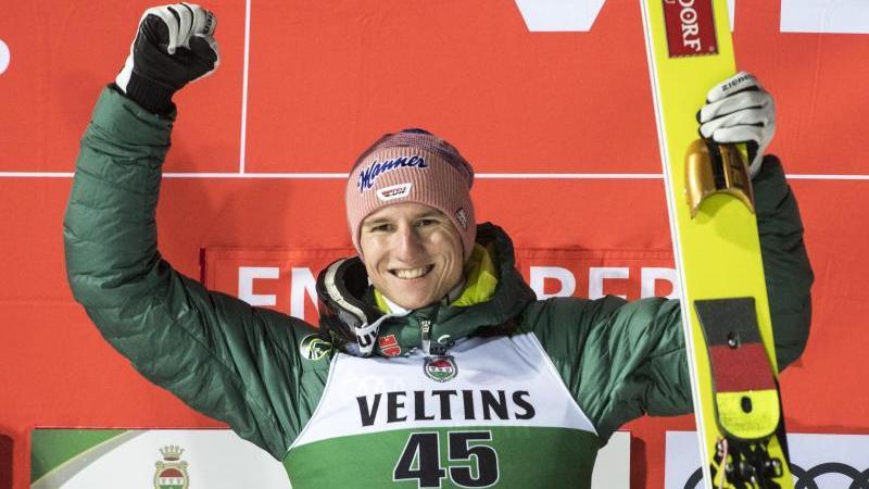 Der Erstplatzierte Karl Geiger bejubelt seinen Sieg auf dem Podium beim Weltcup in Engelber