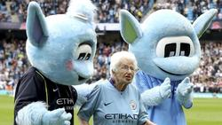 Die 102 Jahre alte Vera Cohen wird von zwei Maskottchen vom Spielfeld geleitet