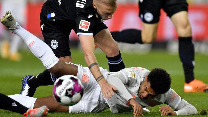 Serge Gnabry vom FC Bayern (unten) im Zweikampf mit Bielefelds Mike van der Hoorn