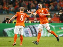 Robin van Persie (r.) wordt in de wedstrijd Nederland - Letland vervroegd naar de kant gehaald. Wesley Sneijder connect nog even met de spits. (16-11-2014)