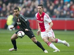 Bilal Ould-Chikh (l.) draait tijdens Ajax - FC Twente behendig weg als Nick Viergever druk wil zetten op de bal. (15-02-2015)