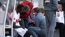 Silas Wamangituka (l.) vom VfB Stuttgart sitzt verletzt auf der Ersatzbank