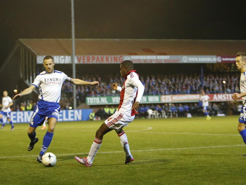 Queensy Menig (r.) probeert een schot van Siemen Lindeboom (l.) te blokken tijdens het bekerduel SV Urk - Ajax. (28-10-2014)