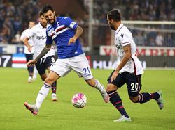 Roberto Soriano (l.) speelt de bal namens Sampdoria langs Domenico Maietta van Bologna. (14-9-2015)