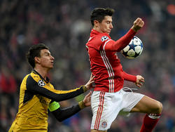 Robert Lewandowski (r.) probeert de bal te controleren, terwijl Laurent Koscielny (l.) in zijn nek hijgt. (15-02-2017)