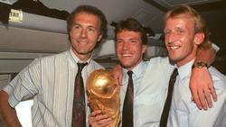 Auf dem Rückflug von Rom präsentieren DFB-Teamchef Franz Beckenbauer (l.), Kapitän Lothar Matthäus (M.) und Andreas Brehme den WM-Pokal