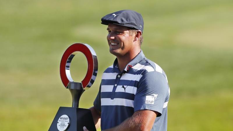 Bryson DeChambeau hält die Trophäe des Golfturniers Rocket Mortgage Classic in den Händen