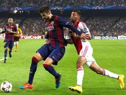 Gerard Piqué (l.) heeft geen problemen met het afhouden van Ricardo Kishna (r.) tijdens het Champions League-duel FC Barcelona - Ajax. (21-10-2014)
