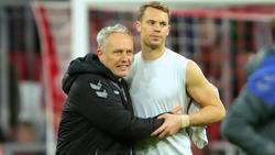 Nach dem Punkt beim FC Bayern sichert sich Christian Streich (l.) noch das Trikot von Manuel Neuer