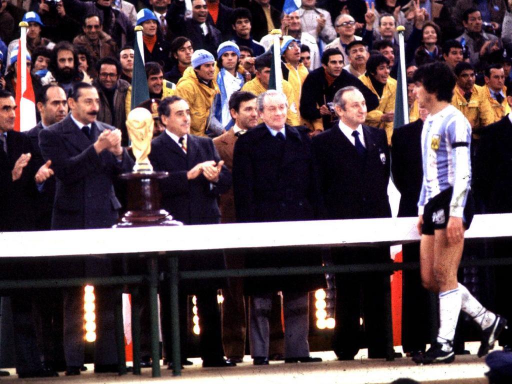 Argentiniens Kapitän Daniel Passarella nimmt den Siegerpokal von Diktator Jorge Rafael Videla (l.) entgegen