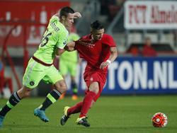 Nick Viergever (l.) kan niets meer dan het shirt van Felipe Gutiérrez vasthouden als de Chileen er met de bal vandoor gaat tijdens de wedstrijd tussen FC Twente en Ajax. (12-09-2015)