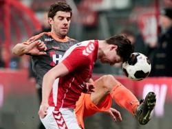 Kees Kwakman (l.) wil een bal wegwerken, maar met gevaar voor eigen leven kopt Maarten Peijnenburg (r.) het speeltuig weg tijdens Jong FC Utrecht - FC Volendam. (13-02-2017)
