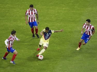 Giovani Dos Santos se intenta zafar de tres rivales.