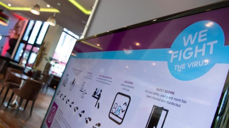 Auf einem Bildschirm in der Lobby des Hotels sind die Hygienemaßnahmen nachzulesen