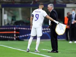 Benzema atiende en la banda a su técnico.