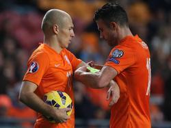 Robin van Persie (r.) schuift de aanvoerdersband om de arm van Arjen Robben (l.) tijdens het EK-kwalificatieduel Nederland - Letland. Voetbal.com Foto van de Week. (16-11-2014)