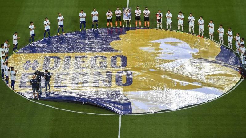 Schiedsrichter und Spieler legen eine Schweigeminute für Maradona ein