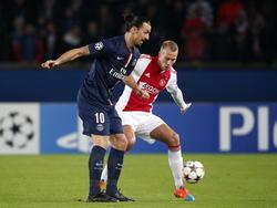 Mike van der Hoorn (r.) is niet bij machte om Zlatan Ibrahimovic (l.) van de bal te krijgen in de Champions League-wedstrijd tussen Paris Saint-Germain en Ajax. (25-11-2014)
